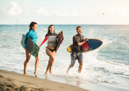 Happy young people running on a beach with surfboards.